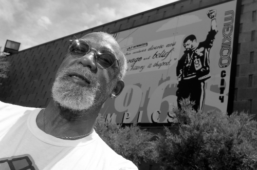 John Carlos, participant of the 1968 Olympics, stands in front of a mural made by students on the campus, at Palm Springs High School